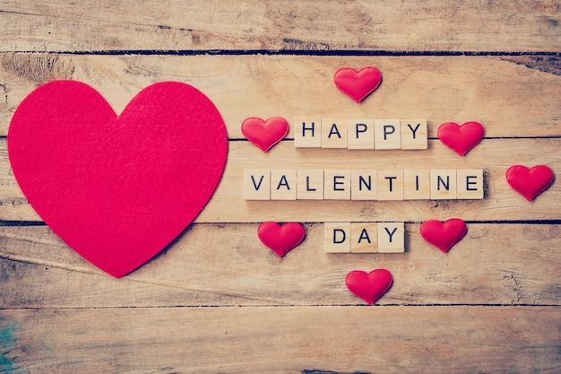 Rode hart met houten tekst gelukkige valentijnsdag op houten tafel achtergrond.