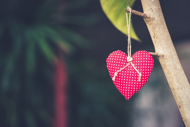Rode hart stof hangend op tak boom met ruimte
