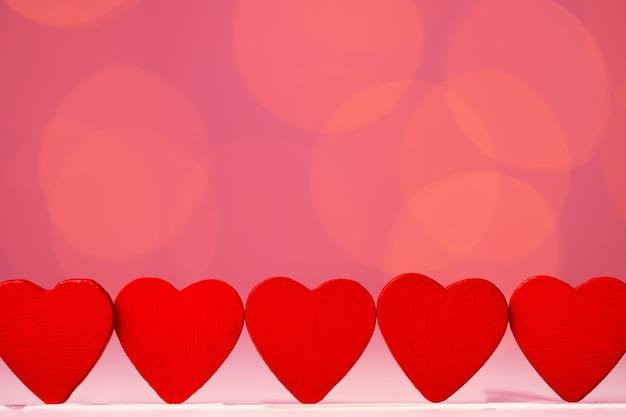 Rode hartdecoratie tegen roze bokeh vooraanzicht