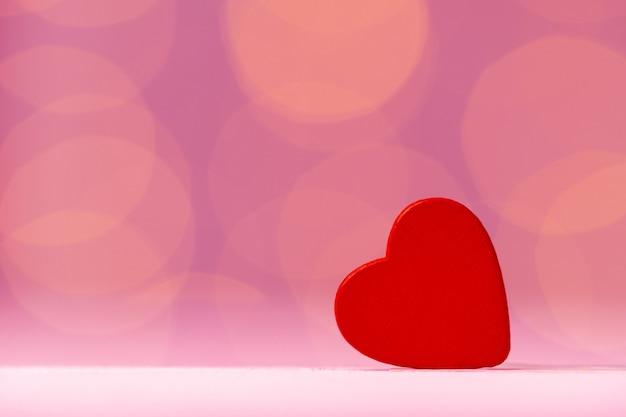 Rode hartdecoratie tegen roze bokeh