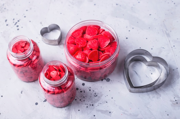 Rode harten als symbool van het poeder van de de dagbanketbakkerij van valentine op een grijze concrete achtergrond.