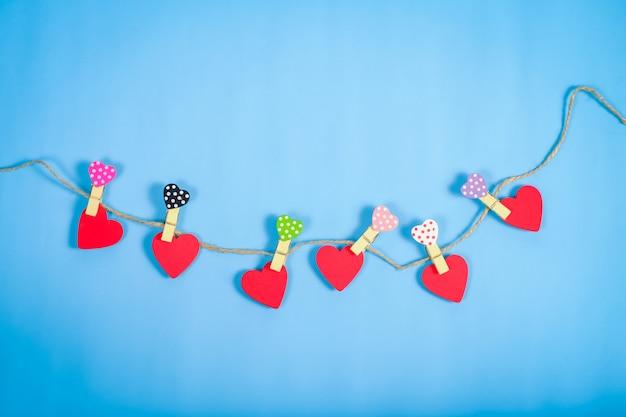 Rode harten die op kabel op kleurenachtergrond hangen