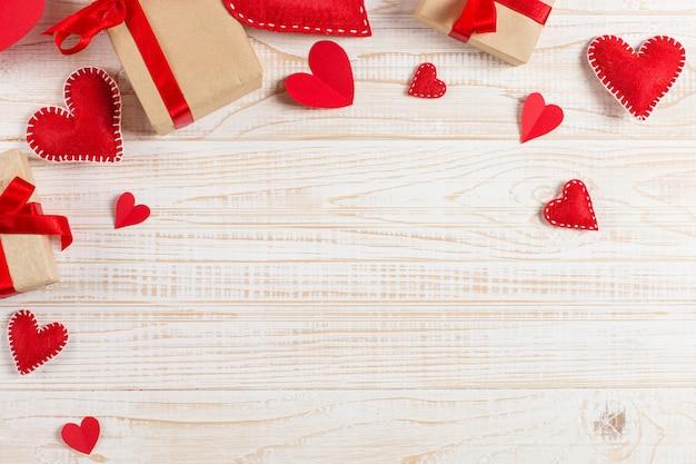 Rode harten en ambachtelijke geschenken op witte houten achtergrond