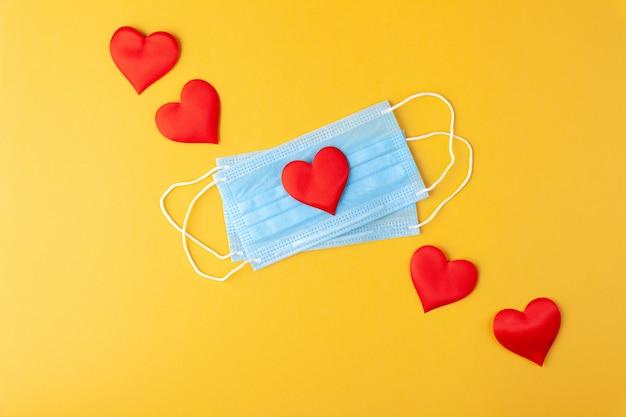 Rode harten en anti-epidemische blauwe medische maskers, wegwerp medische benodigdheden, concept valentijnsdag, liefde, dankzij artsen, kopie ruimte, horizontaal, gele muur