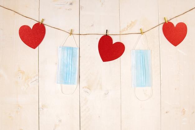 Rode harten en chirurgische gezichtsmaskers die op koord op witte houten achtergrond hangen.