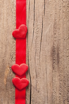 Rode harten en lint frame houten achtergrond voor valentijnsdag
