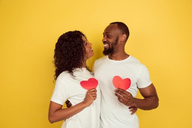 Rode harten houden. valentijnsdagviering, gelukkig afrikaans-amerikaans paar dat op gele studioachtergrond wordt geïsoleerd. concept van menselijke emoties, gezichtsuitdrukking, liefde, relaties, romantische vakanties.