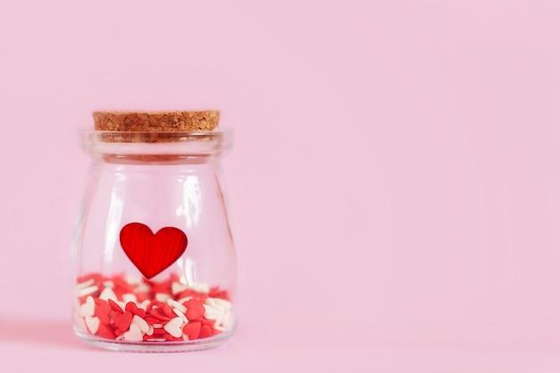 Rode harten in een glazen pot op roze muur.