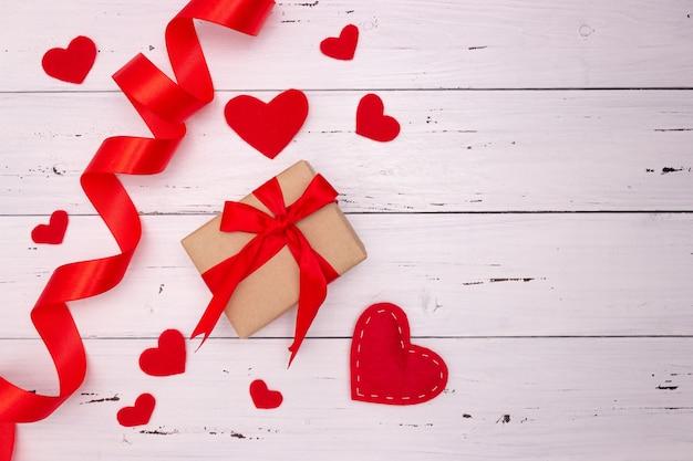 Rode harten, lint en cadeau op witte houten achtergrond. bovenaanzicht, vrije ruimte voor tekst. valentijnsdag, liefde.