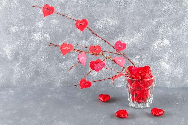 Rode harten met een inscriptie liefde hangen takken op een grijze concrete achtergrond. liefdesboom.