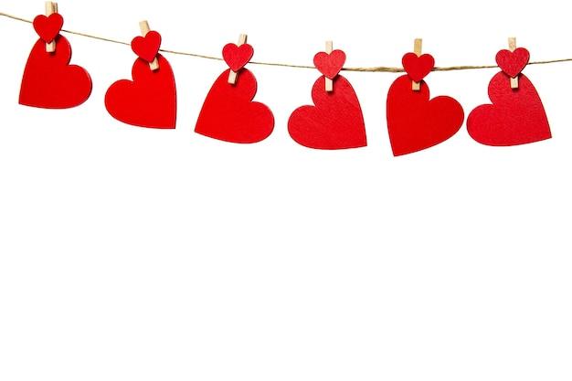 Rode harten met wasknijpers die met geïsoleerde kabel hangen. valentijnsdag