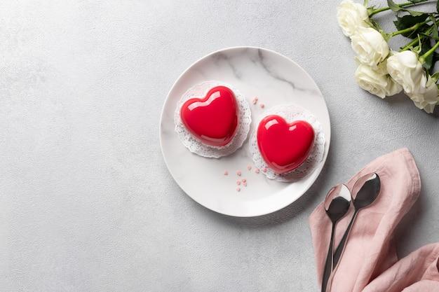 Rode harten mousse cakes en boeket van witte rozen