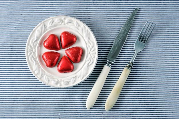 Rode harten op een bord en een mes met een vork