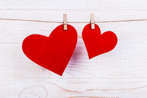 Rode harten op een touw met wasknijpers, op een witte houten achtergrond. plaats voor tekst, kopieer ruimte.