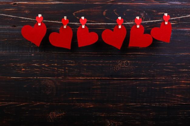 Rode harten op een touw met wasknijpers, op een zwarte houten achtergrond. plaats voor tekst, kopieer ruimte.