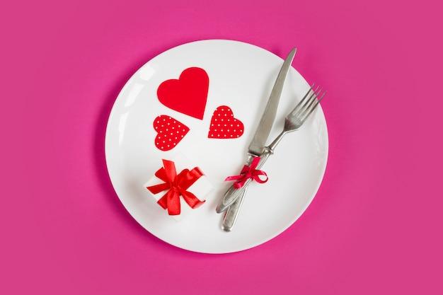 Rode harten op een witte plaat, een vork, een mes, een geschenkdoos op roze