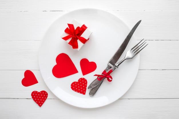 Rode harten op een witte plaat, een vork, een mes, een rood lint, een geschenkdoos op een witte houten tafel