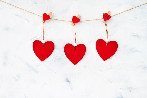 Rode harten op het touw op witte achtergrond. valentijnsdag achtergrond. ruimte kopiëren