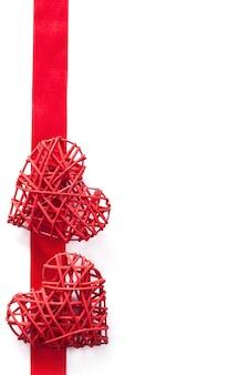 Rode harten over de achtergrond van het lintkader voor geïsoleerde valentijnskaarten