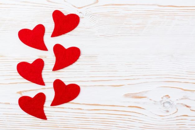Rode harten van vilt op een witte houten achtergrond