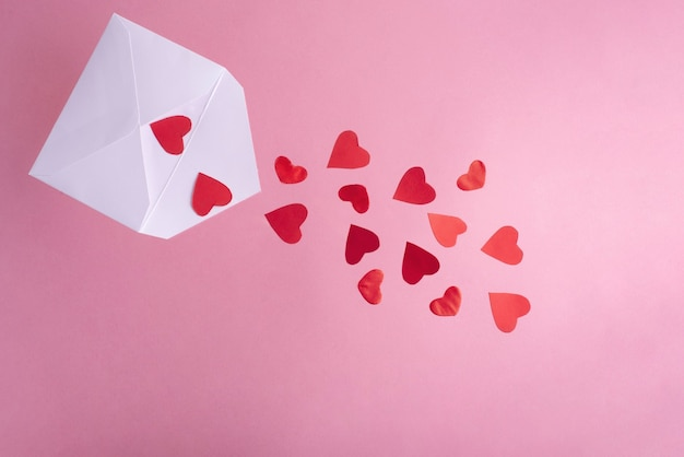 Rode harten vliegen uit een witte envelop, close-up. valentijnsdag.