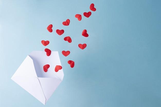 Rode harten vliegen uit een witte envelop, valentijnsdag.