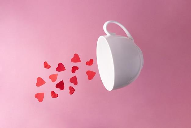 Rode harten vliegen uit een witte kop, close-up. valentijnsdag.