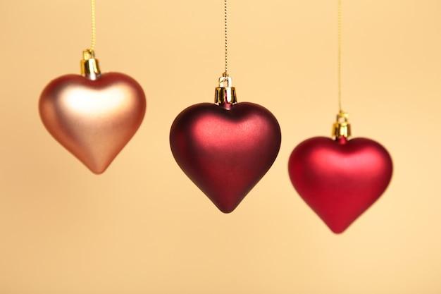Rode harten voor kerstversiering op beige achtergrond.