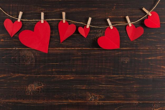 Rode harten worden vastgehouden door wasknijpers aan jutetouw, op donker hout. kopieer ruimte
