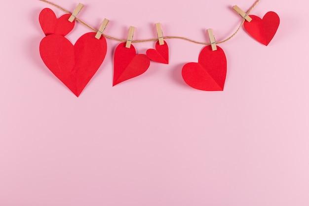 Rode harten worden vastgehouden door wasknijpers aan jutetouw, op roze achtergrond. kopieer ruimte.
