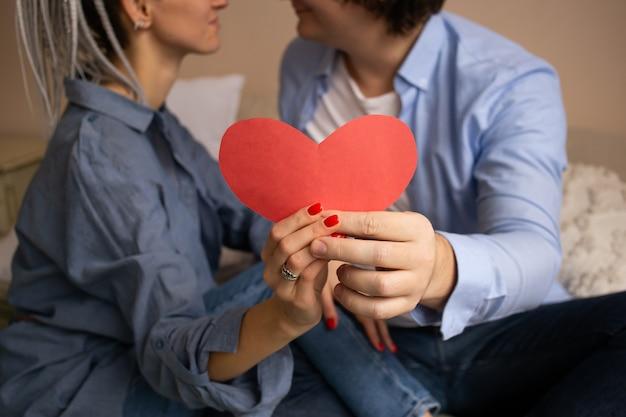 Rode hartvalentijnskaart in handen. paar in slaapkamer zittend op bed en knuffelen.