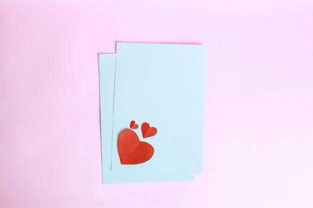 Rode hartvorm op wit envelopdocument dat op roze achtergrond wordt geïsoleerd