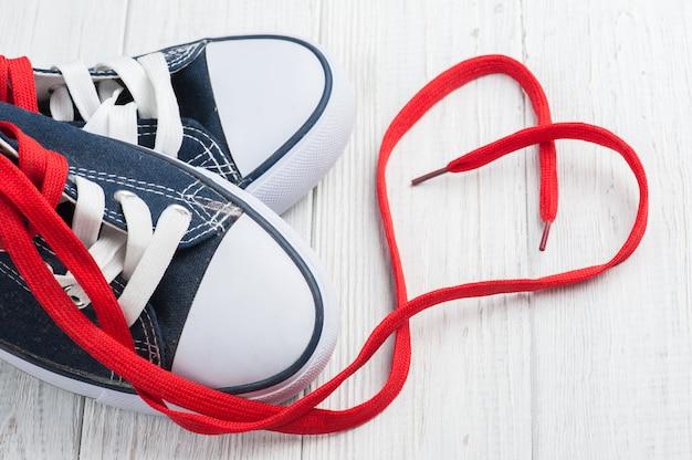 Rode hartvorm van veters en blauwe sneakers