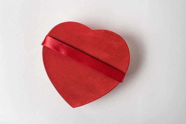 Rode hartvormige doos met lint op de witte achtergrond. bovenaanzicht. cadeau voor valentijnsdag
