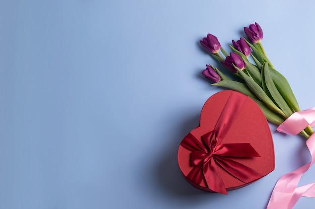 Rode hartvormige geschenkdoos en vers tulpenboeket