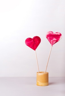Rode hartvormige lollies op een witte achtergrond. briefkaart voor de dag van sint-valentijn. romantisch liefdesverhaal met copyspace.