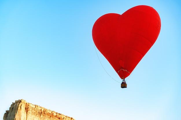 Rode hartvormige luchtballon die in de heldere hemel vliegt