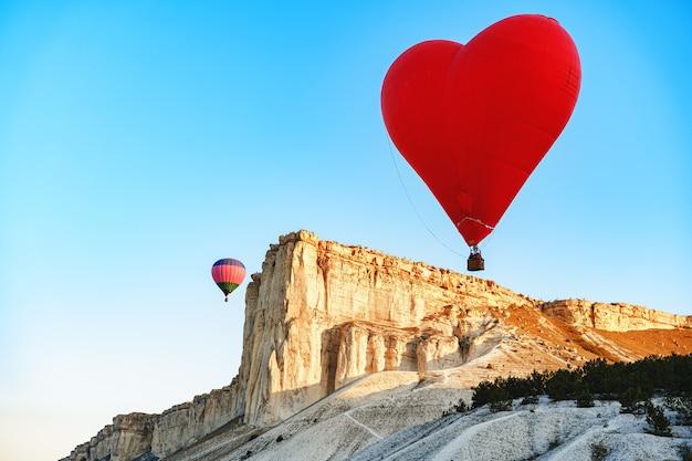Rode hartvormige luchtballon die in de lucht vliegt