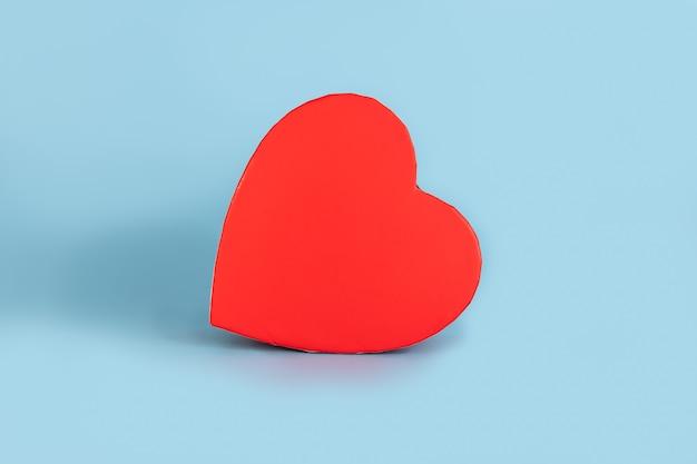 Rode hartvormige valentijnsdag geschenkdoos geïsoleerd op blauwe achtergrond met kopie ruimte voor tekst en afbeeldingen