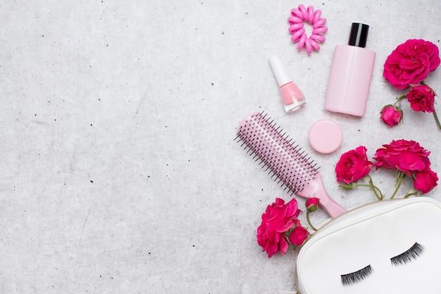 Rode heldere rozen en make-upaccessoires op een lichtgrijze achtergrond