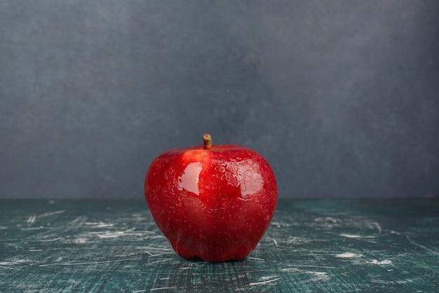 Rode hele appel op blauwe achtergrond.