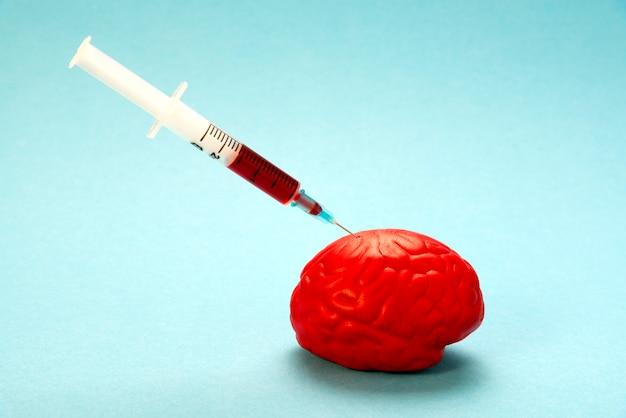 Rode hersenen op blauw met een nootropische spuit.
