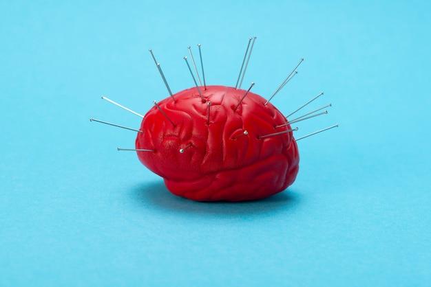 Rode hersenen op een blauwe achtergrond met geïnjecteerde naalden.