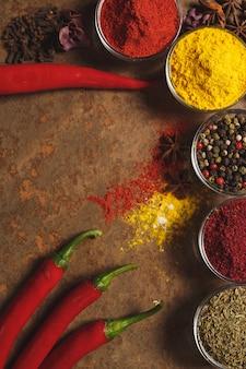 Rode hete chili pepers. plaats voor tekst. verschillende soorten kruiden in een kom op een stenen muur. het uitzicht vanaf de top