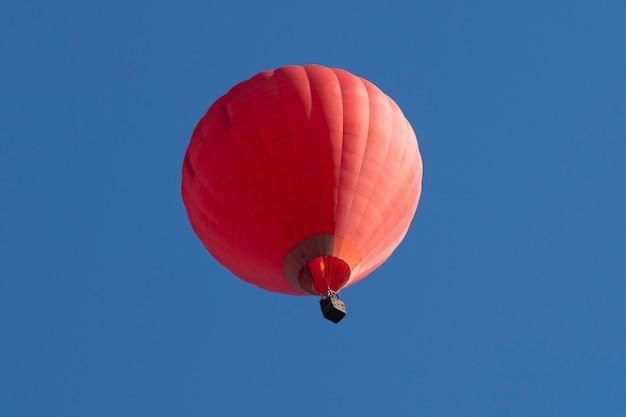 Rode hete luchtballons die in blauwe hemel vliegen