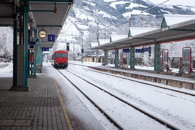 Rode hogesnelheidstrein voor passagiers stopt bij een verlaten, met sneeuw bedekt treinstation in de bergen.