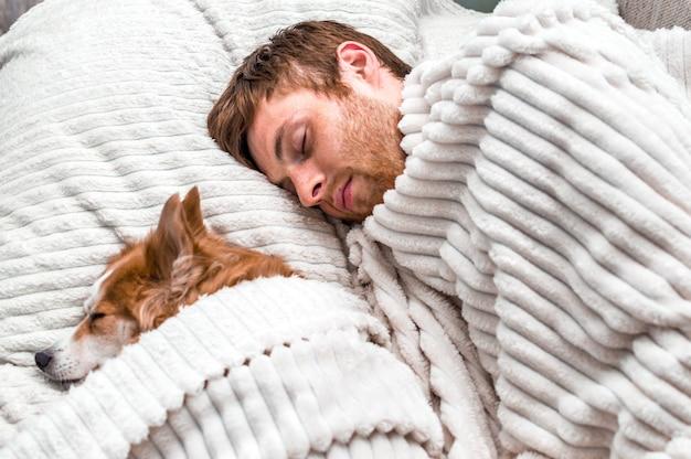 Rode hond slaapt in een roze slaapmasker met zijn baasje in bed. concept weekend en rust