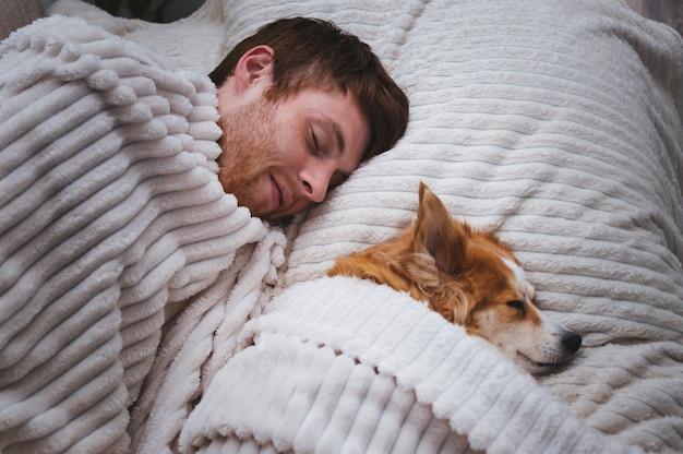 Rode hond slaapt masker met zijn baasje in bed. concept weekend en rust