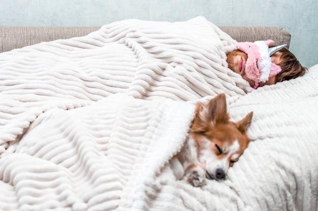 Rode hond slaapt met zijn baasje in een roze slaapmasker in het bed. concept weekend en rust