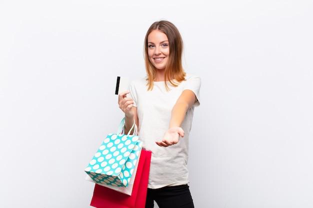 Rode hoofd mooie vrouw die gelukkig met vriendschappelijke, zekere, positieve blik glimlacht, een voorwerp of concept met het winkelen zakken aanbiedt en toont